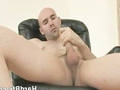 Good looking vidz man sits  super on the couch and plays with his white dick
