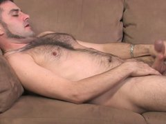 Hairy stud vidz lays on  super the couch and starts playing with his hard pole